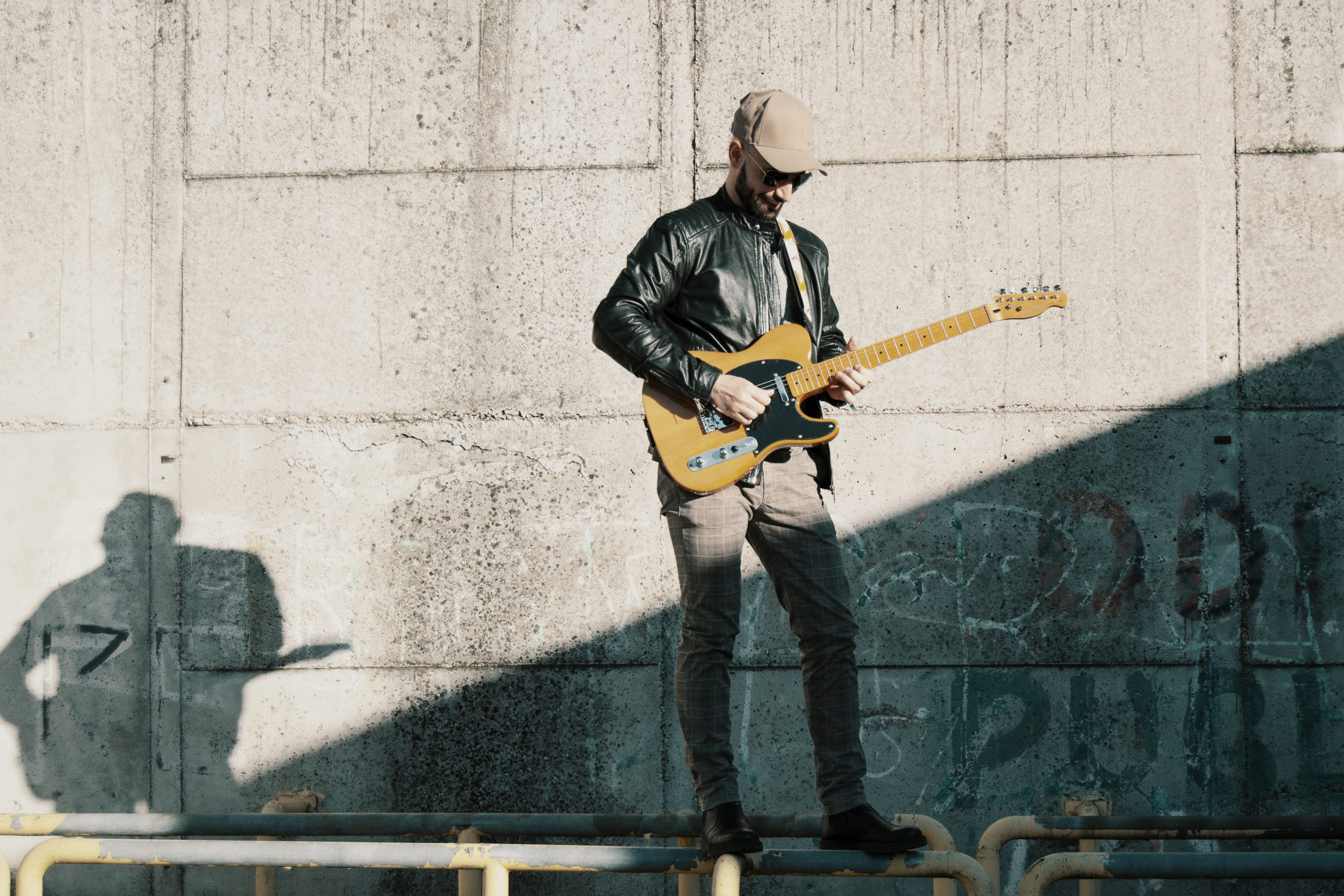 Guitar player in front of a stadium